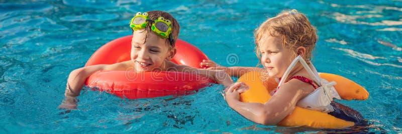 Duas crianças que jogam na BANDEIRA da piscina, FORMATO LONGO imagens de stock