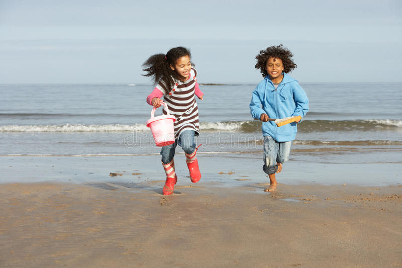 Duas crianças que jogam pela praia do inverno de Mar  foto de stock
