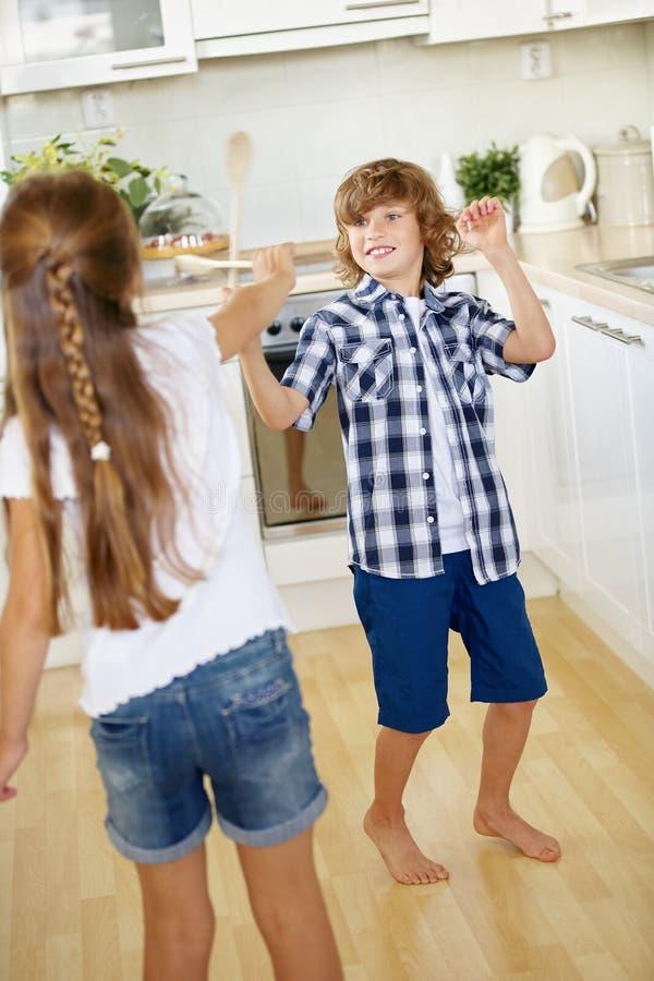 Duas crianças que lutam com as colheres de madeira no divertimento imagem de stock