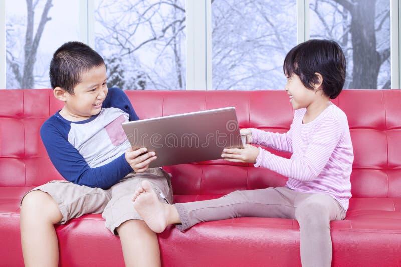 Duas crianças que lutam para tomar sobre o portátil imagem de stock royalty free