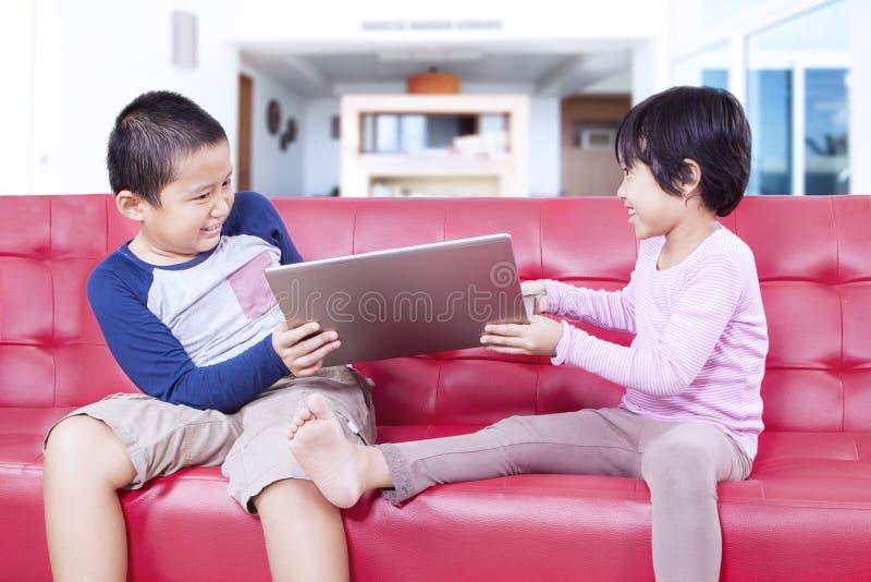 Duas crianças que lutam sobre um caderno fotos de stock