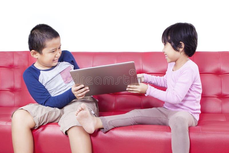 Duas crianças que lutam sobre um portátil imagens de stock royalty free