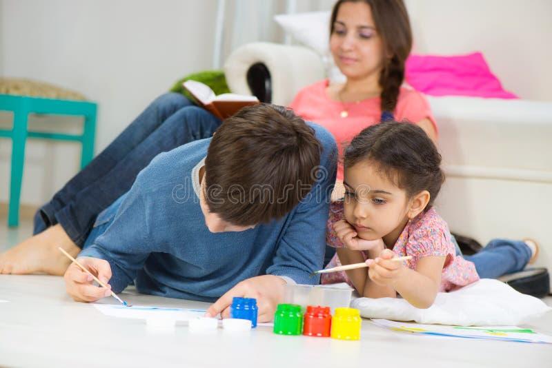 Duas crianças que pintam com pinturas coloridas em casa fotografia de stock