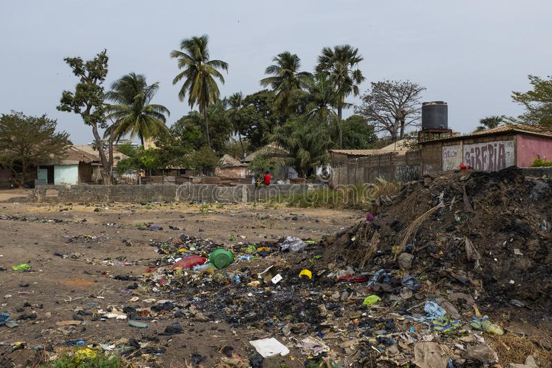 Duas crianças que sentam-se em uma parede perto de uma pilha do lixo na vizinhança de Bandim se a cidade de Bissau foto de stock