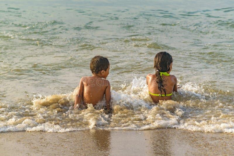 Duas crianças que sentam-se na costa da praia foto de stock