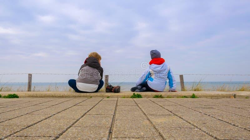 Duas crianças que sentam-se para baixo nos pavimentos e que olham o mar, vestindo-se densamente com o céu azul com nuvens branc fotografia de stock royalty free