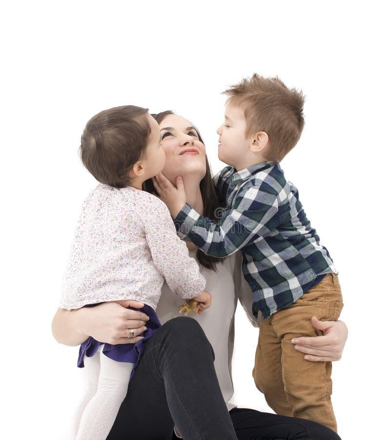 Duas crianças que têm o divertimento com sua mãe imagem de stock