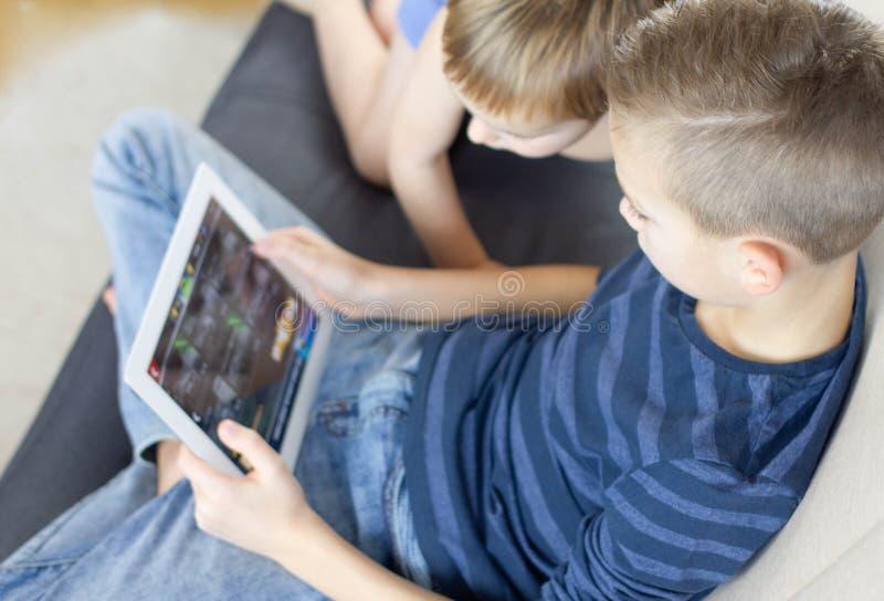 Duas crianças que usam a tabuleta em casa Irmãos com o tablet pc na sala clara Meninos que jogam jogos no PC da tabuleta, emoções imagens de stock royalty free