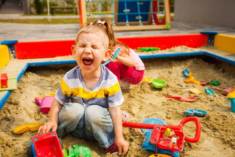 Duas crianças ranhosas brincando na caixa de areia foto de stock