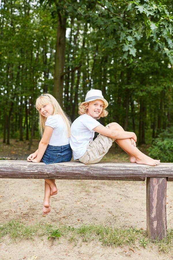 Duas crianças são sentar-se relaxado em um parque fotos de stock royalty free