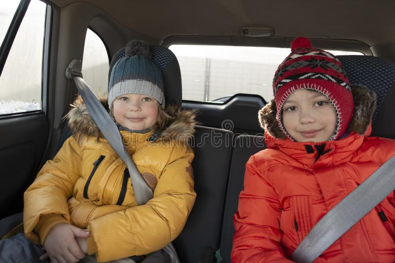 Duas crian?as no carro que um inverno alegre trope?a imagens de stock