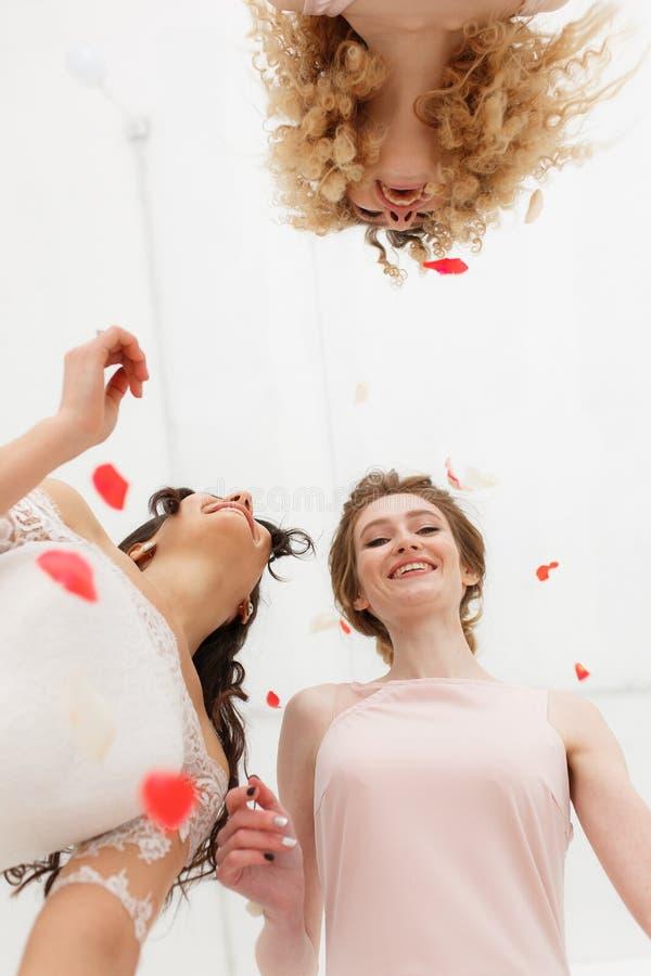Duas damas de honra que têm o divertimento com noiva Retrato do close-up de baixo nas pétalas do voo Casamento bege elegante imagens de stock