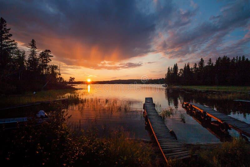 Duas docas no por do sol sobre o lago fotografia de stock