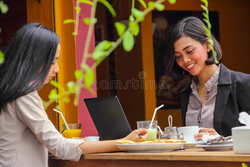 Duas empresárias asiáticas passaram o horário de almoço num café ao ar livre imagem de stock royalty free