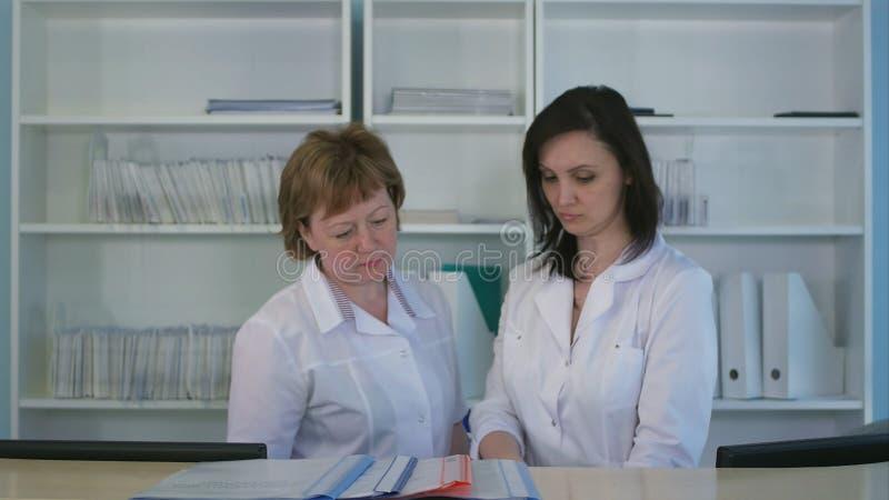 Duas enfermeiras que classificam para fora dobradores e arquivos na mesa de recepção do hospital fotos de stock
