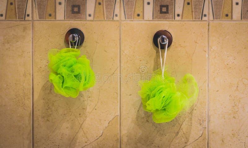 Duas esponjas verdes do banho que penduram da parede do banheiro foto de stock