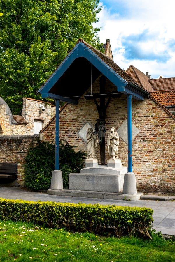 Duas estátuas brancas abaixo de um telhado de inclinação na cidade de Bruges, B imagens de stock