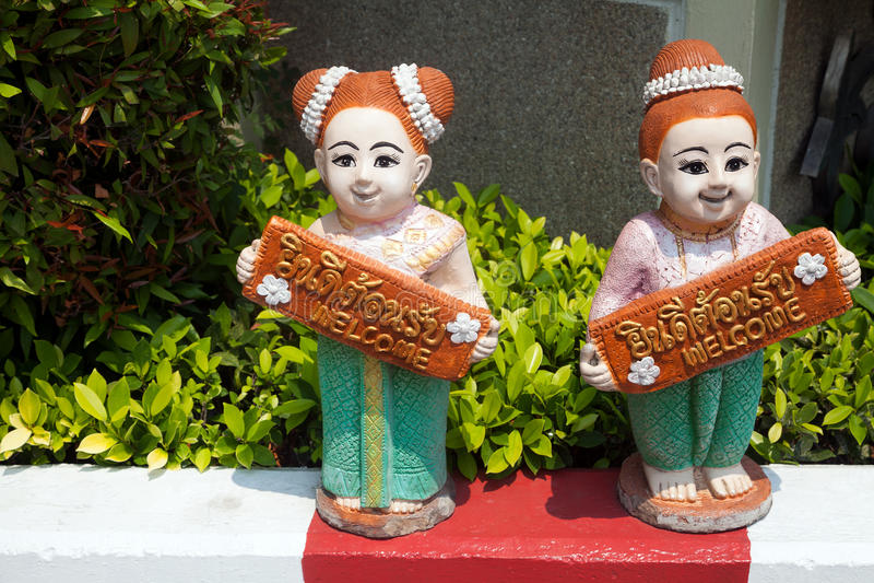 Duas estatuetas cerâmicas das meninas tailandesas que guardam bem-vindas assinam dentro inglês e tailandês imagens de stock