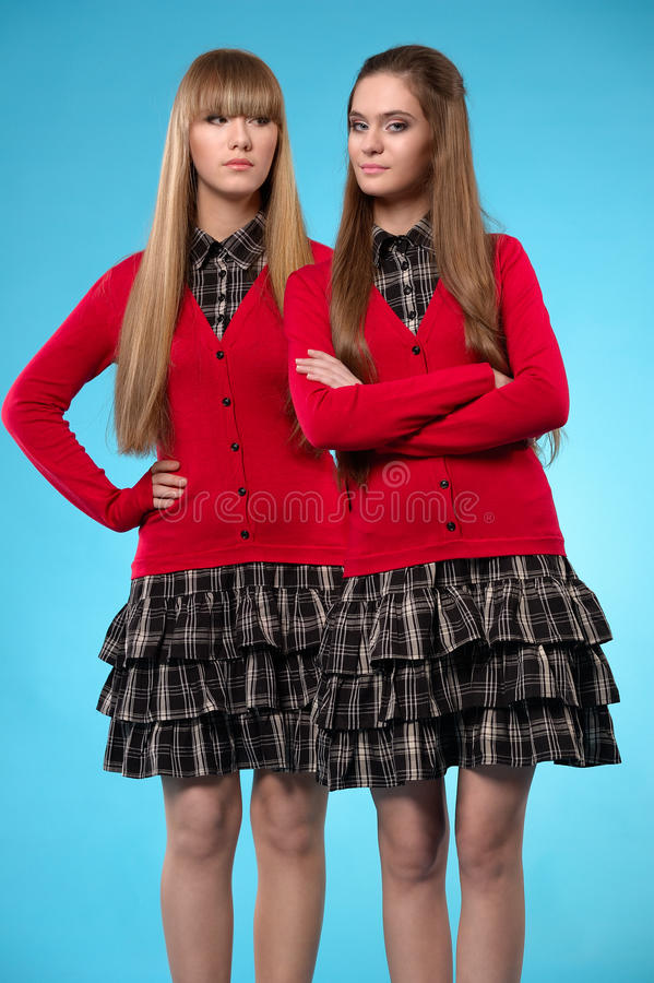 Duas estudantes adolescentes estão de lado a lado sobre o fundo azul imagens de stock royalty free