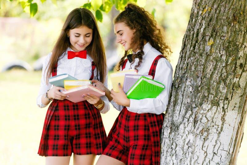 Duas estudantes bonitas no suporte da farda da escola com livros fora no parque fotografia de stock royalty free