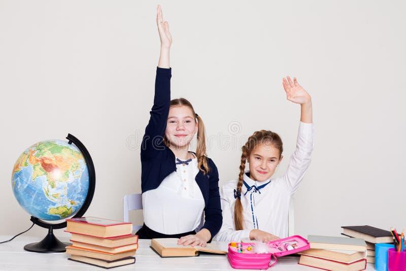 Duas estudantes das meninas que sentam-se em sua mesa na lição na escola foto de stock