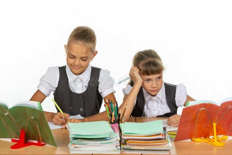 Duas estudantes em uma mesa, uma com um bom humor, a outro com um mau fotografia de stock royalty free
