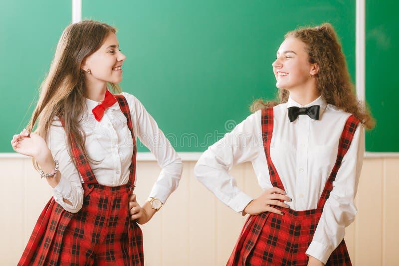 Duas estudantes engraçadas na farda da escola estão estando com os livros no fundo da administração da escola foto de stock royalty free