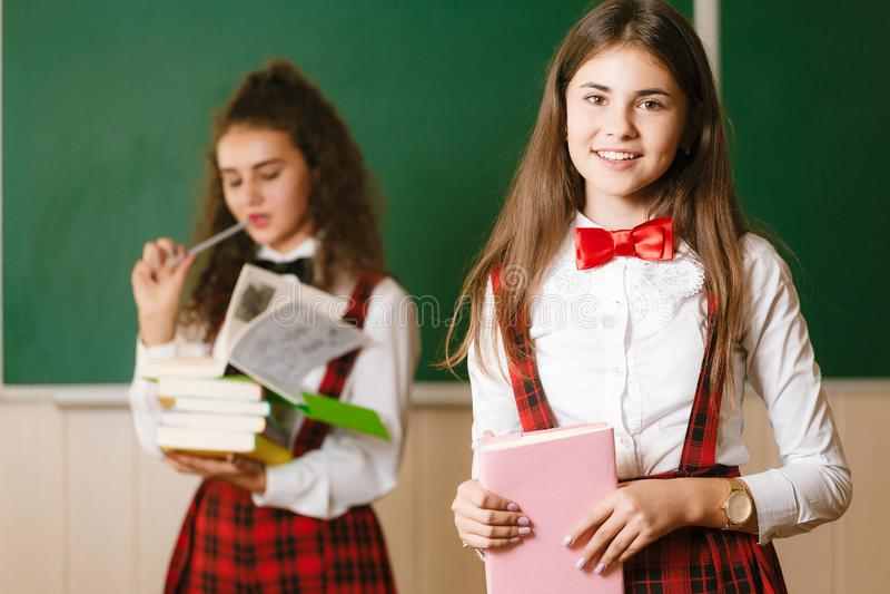Duas estudantes engraçadas na farda da escola estão estando com os livros no fundo da administração da escola fotografia de stock