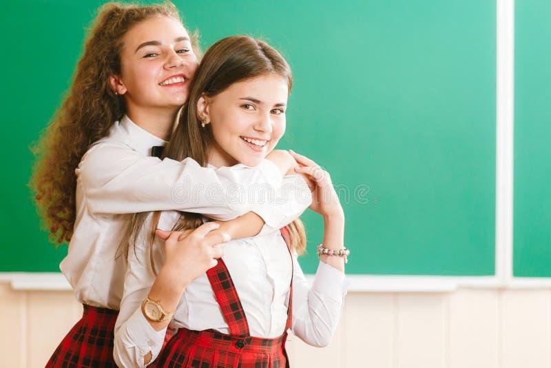 Duas estudantes engraçadas na farda da escola estão estando com os livros no fundo da administração da escola fotos de stock