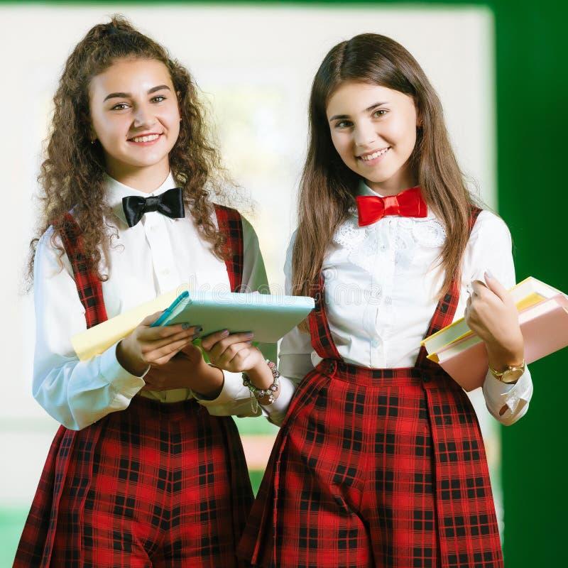 Duas estudantes estão estando no corredor com livros fotografia de stock royalty free