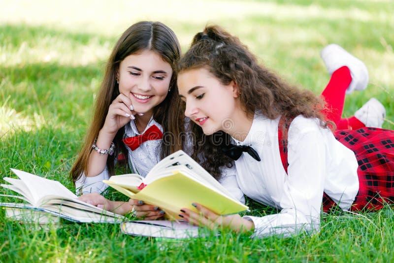 Duas estudantes nas fardas da escola sentam-se com os livros no parque As estudantes ou os estudantes são ensinados lições na nat imagem de stock royalty free