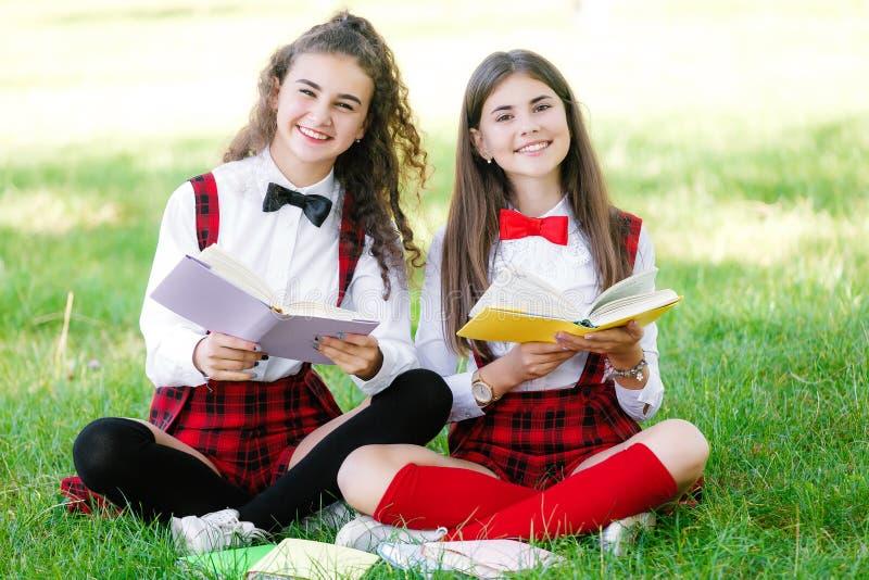Duas estudantes nas fardas da escola sentam-se com os livros no parque As estudantes ou os estudantes são ensinados lições na nat foto de stock