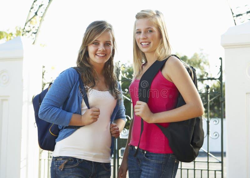 Duas estudantes universitário fêmeas que estão a porta exterior fotografia de stock royalty free