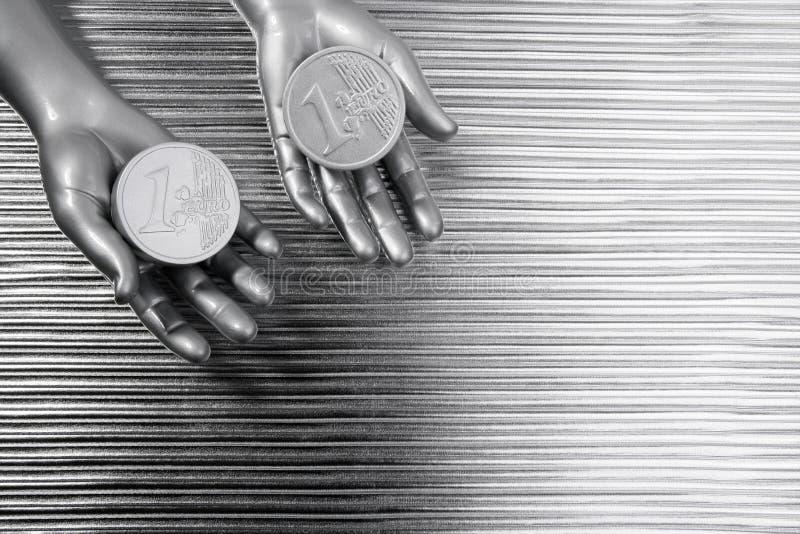 Duas euro- moedas de prata nas mãos futuristas do robô foto de stock royalty free