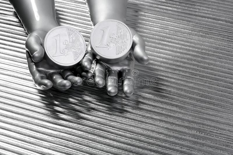 Duas euro- moedas de prata nas mãos futuristas do robô fotografia de stock