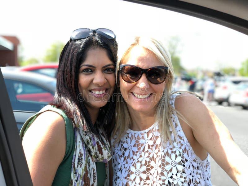 Duas fêmeas atrativas da raça misturada sorriem e olham a câmera fotos de stock royalty free