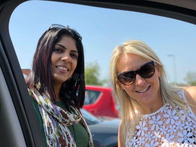 Duas fêmeas atrativas da raça misturada sorriem e olham a câmera fotos de stock