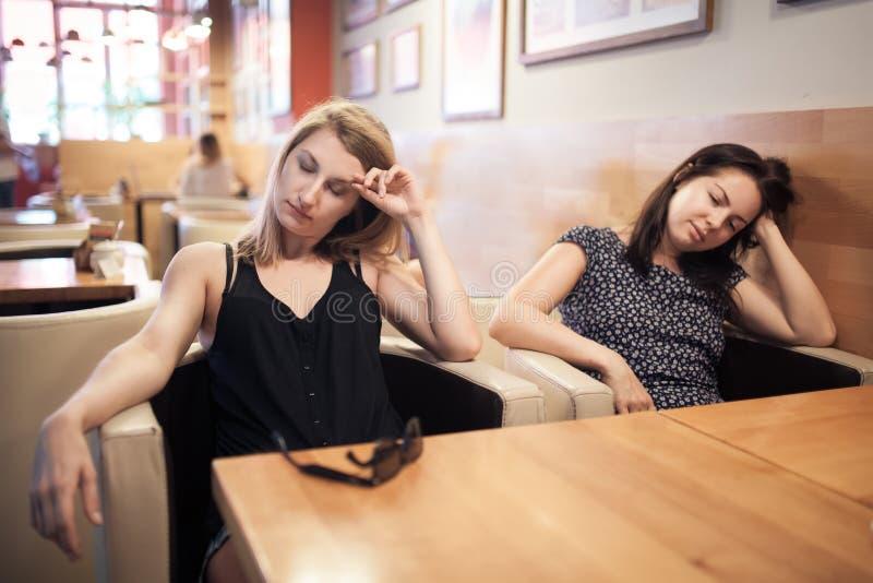 Duas fêmeas cansados que sentam-se no café e no descanso; fotografia de stock