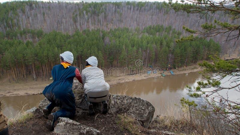 Duas fêmeas caucasianos novas em um perigo do penhasco que olha para baixo ao rio fotos de stock royalty free