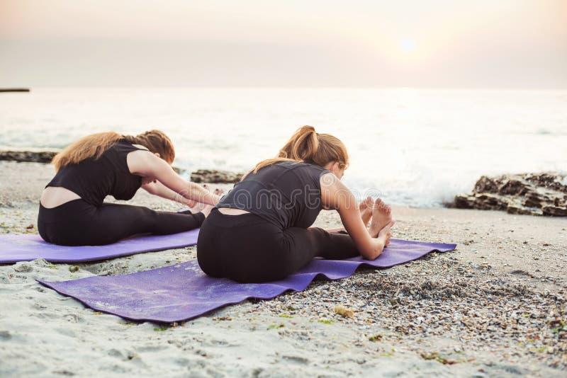 Duas fêmeas caucasianos novas que praticam a ioga na praia imagem de stock royalty free