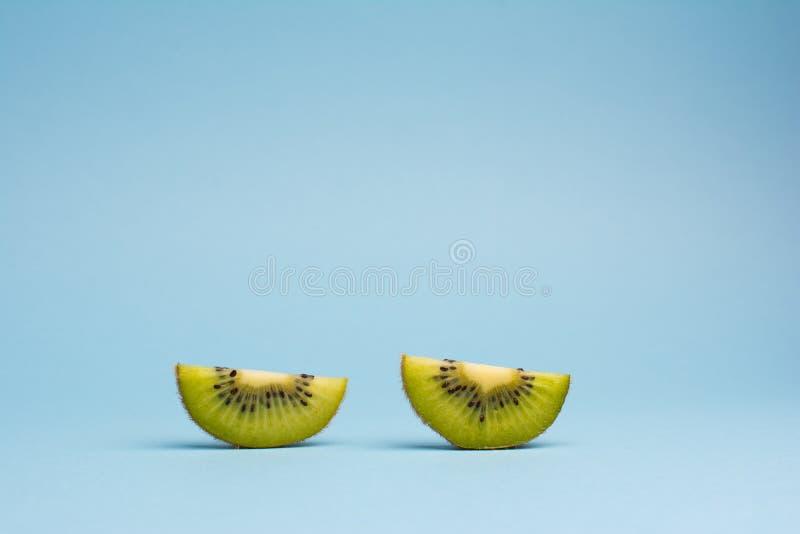Duas fatias de fruto de quivi no fundo azul fotos de stock royalty free