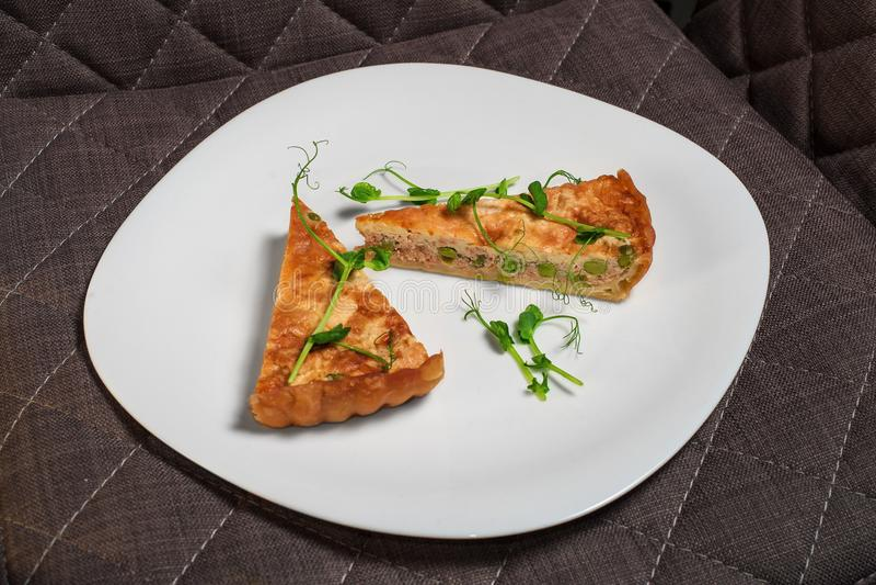 Duas fatias de torta do sopro dos salmões com ervilhas e verdes fotos de stock