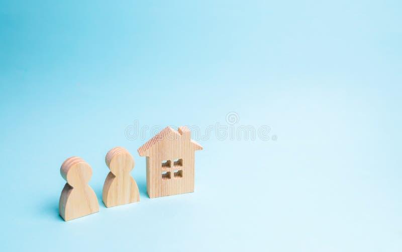 Duas figuras dos povos e de uma casa de madeira em um fundo azul O conceito do alojamento disponível e das hipotecas para comprar fotografia de stock royalty free