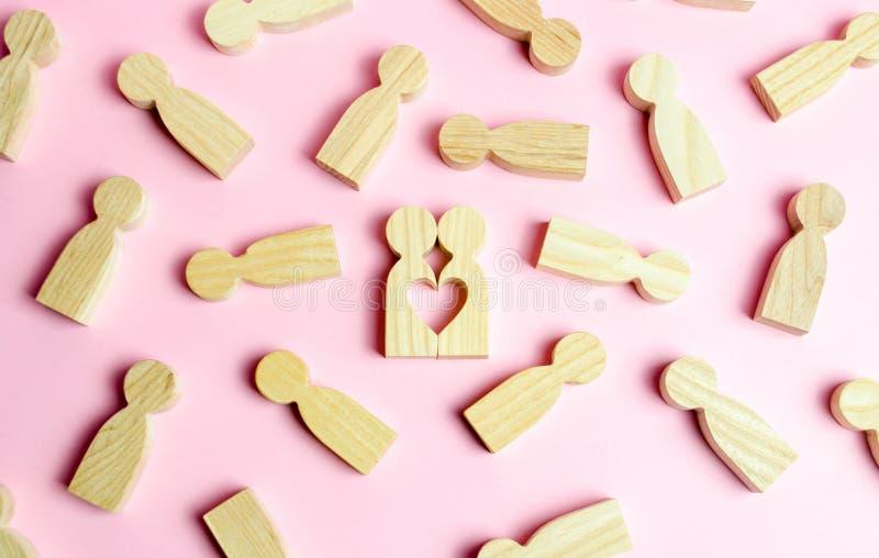 Duas figuras humanas formam junto um vácuo na forma de um coração em um fundo cor-de-rosa Conceito do amor e da busca fotos de stock royalty free