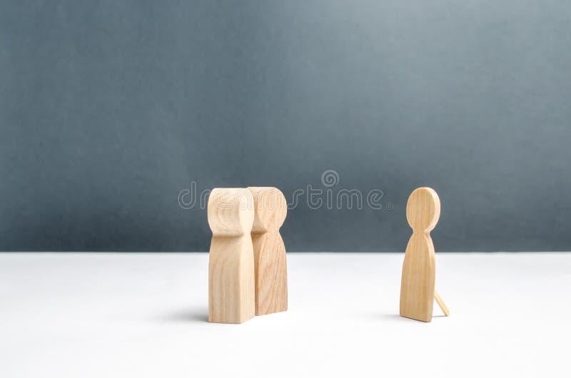 Duas figuras humanas olham uma figura humana falsa O conceito da decepção e do mosheynik Não há nenhuns interesse comum e assunto fotografia de stock
