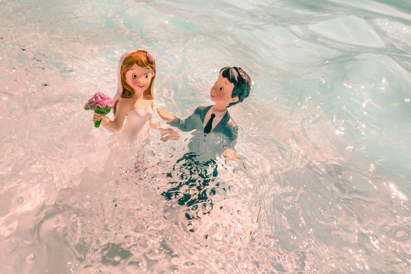 Duas figurinas, o marido e sua esposa, o dia do casamento, tomando banho na água como um ritual de amor imagem de stock