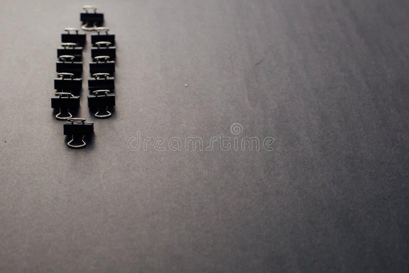 Duas fileiras de clipes de papel de aço pretos na esquerda de um fundo preto imagem de stock royalty free