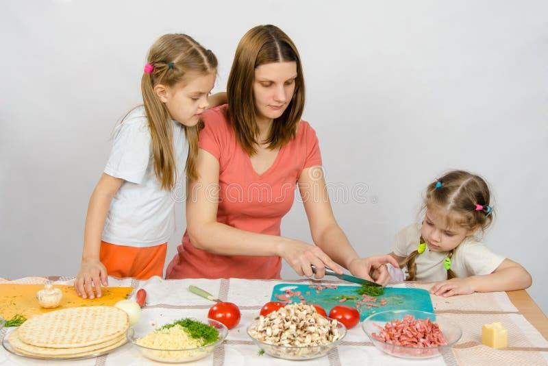 Duas filhas estão olhando com interesse como a mãe desbastou o verde fotos de stock