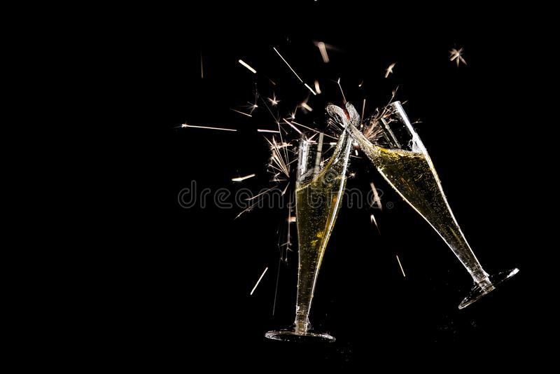 Duas flautas de champanhe, brinde com respingo e chuveirinhos contra a foto de stock royalty free