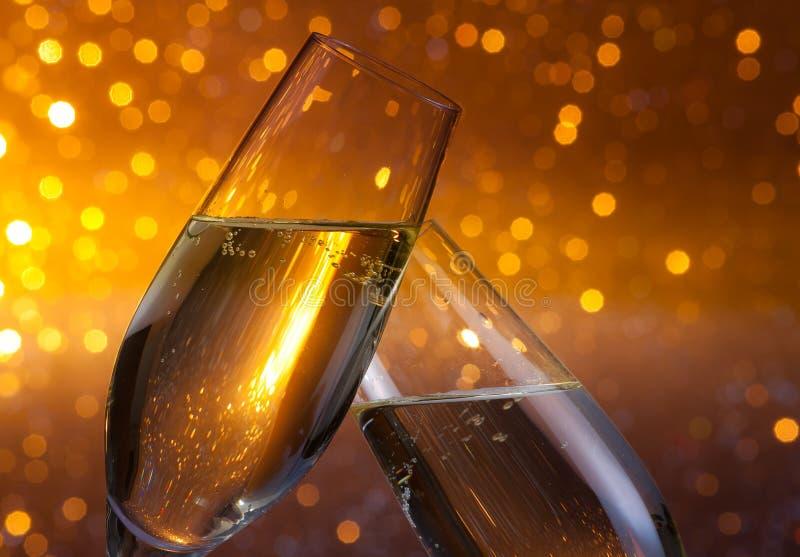 Duas flautas de champanhe com ouro borbulham no fundo claro escuro do bokeh imagem de stock
